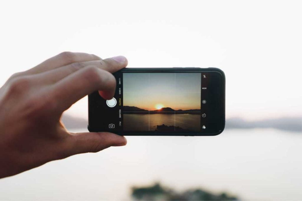 Image of person holding an oPhone taking a picture of a sunset